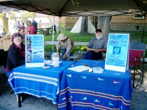 Hamilton Farmers Market Sleeping Child Hot Springs for All booth, with volunteers Tom Potts, Natalie Harper and Eve Meng.
